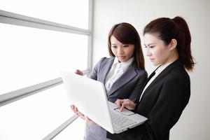 le donne d'affari guardano e sorridono conversazione foto