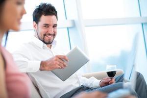 uomo d'affari con tavoletta digitale e bicchiere di vino foto