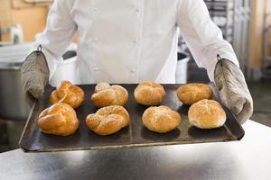 fornaio mostrando vassoio di panini foto