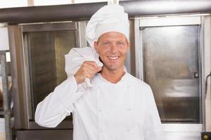 fornaio sorridente tenendo la borsa di farina