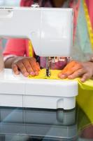 stilista che utilizza la macchina da cucire foto