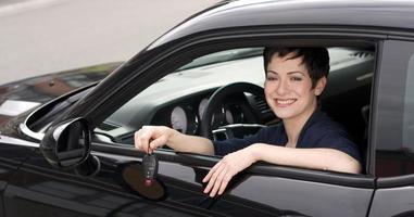 chiavi della berlina nera sorridente agente di noleggio auto femminile sorridente foto