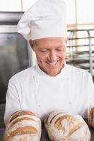 felice fornaio mostrando vassoio di pane fresco foto