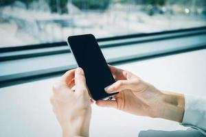 smartphone che tiene in mano femmina sullo sfondo blured. orizzontale foto