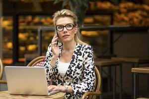 donna di affari che si siede in caffè all'aperto con il computer portatile foto