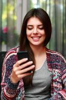 donna attraente che per mezzo dello smartphone foto