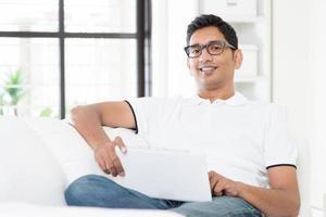 uomo indiano che per mezzo della compressa del computer digitale foto