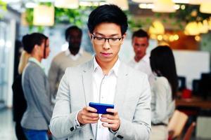 uomo d'affari asiatico tramite smartphone foto