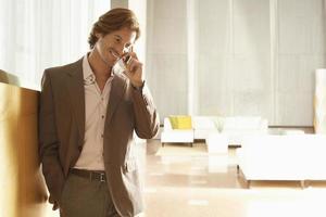 uomo d'affari che utilizza telefono cellulare nell'ufficio foto