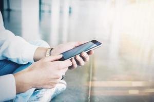 donna seduta sul pavimento e tenendo il suo smartphone dentro foto