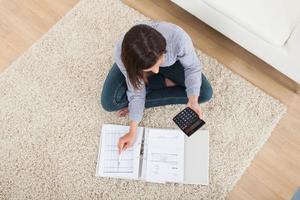 donna calcolando le finanze domestiche sul tappeto foto