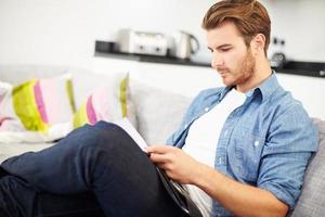 giovane uomo guardando attraverso le finanze personali a casa foto