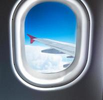 finestra dell'aeroplano che vola sopra le nuvole foto