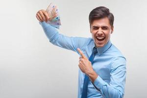 uomo d'affari che celebra il reddito di denaro contro il fondo bianco foto