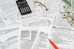 calcolo della dichiarazione dei redditi con denaro e penna foto