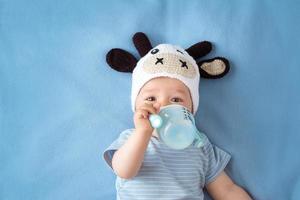 bambino in un cappello da mucca bere latte foto