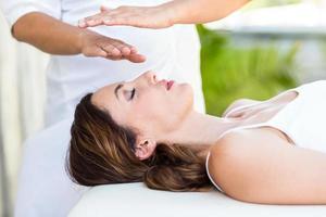 donna calma che riceve un trattamento reiki foto