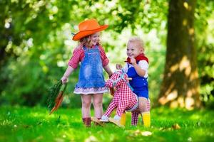 bambini da cowboy che giocano con il cavallo giocattolo foto