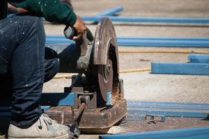 taglio dell'acciaio con macchina per il taglio dell'acciaio da parte del lavoratore foto