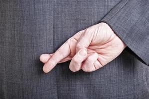 uomo in giacca e cravatta con le dita incrociate dietro la schiena