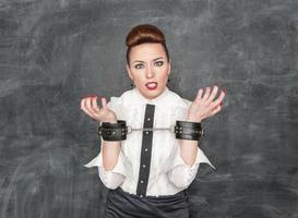 donna d'affari con le manette sulle sue mani foto