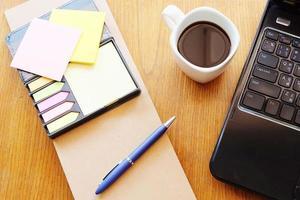 taccuino e computer portatile sulla tavola di legno con caffè foto
