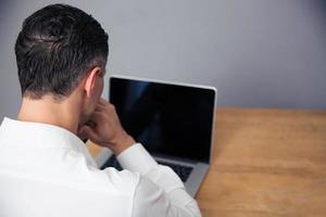 uomo d'affari che per mezzo del computer portatile con lo schermo in bianco foto