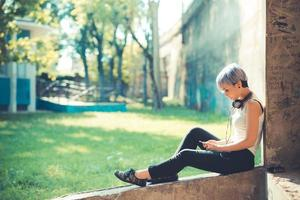 donna giovane hipster bella bella capelli corti blu con cuffie mu foto