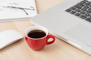 tazza di caffè e laptop in ufficio foto