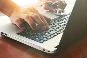 medico che lavora con tavoletta digitale e computer portatile foto