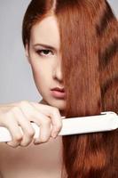 donna dai capelli rossi con capelli stiratura ferri da stiro foto