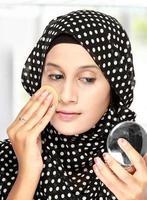 donna con un batuffolo di cotone che applica cipria foto