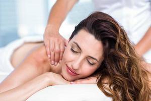 brunette sorridente che ottiene massaggio posteriore foto