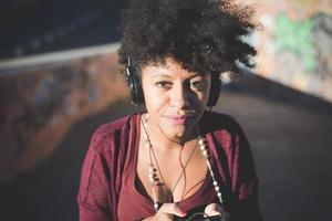 bella musica d'ascolto della donna africana dei bei capelli ricci neri con lui foto