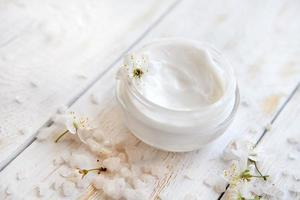 vaso di crema di bellezza circondato da fiori e sale marino foto