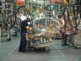 dipendenti che costruiscono diligentemente nuove automobili foto