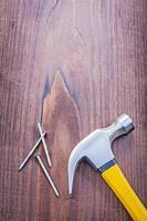 martello da carpentiere con chiodi su tavola di legno vintage copyspace co foto