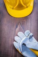 casco guanto martello da carpentiere su tavola di legno d'epoca foto