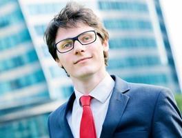 Ritratto all'aperto di un dinamico junior executive sorridente foto
