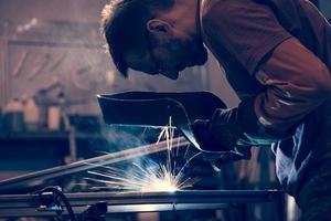 un lavoratore che salda acciaio in un'officina foto