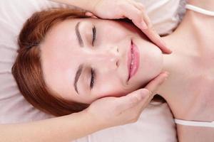 la giovane donna gode del massaggio del viso foto
