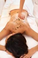 la donna ottiene un trattamento di avvolgimento di alghe marine nel salone spa foto
