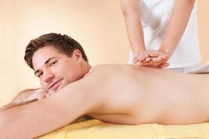 uomo che riceve massaggio alla schiena nella spa foto