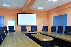 sala conferenze con sedie vuote e schermo per proiettore foto