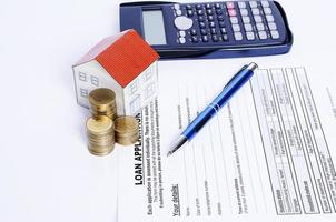penna blu con pila di monete e carta casa e calcolatrice foto