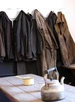 vecchie tute da lavoro e cappotti appesero alla fine del turno foto