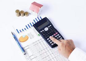 calcolatrice e grafico finanziario con penna e monete con casa foto