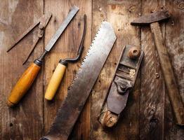 od utensili a mano vintage su fondo in legno. posto di lavoro del carpentiere foto
