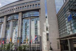 palazzo del parlamento dell'ue a Bruxelles con le bandiere di paese foto