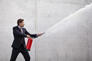 uomo d'affari focalizzato utilizzando un estintore foto